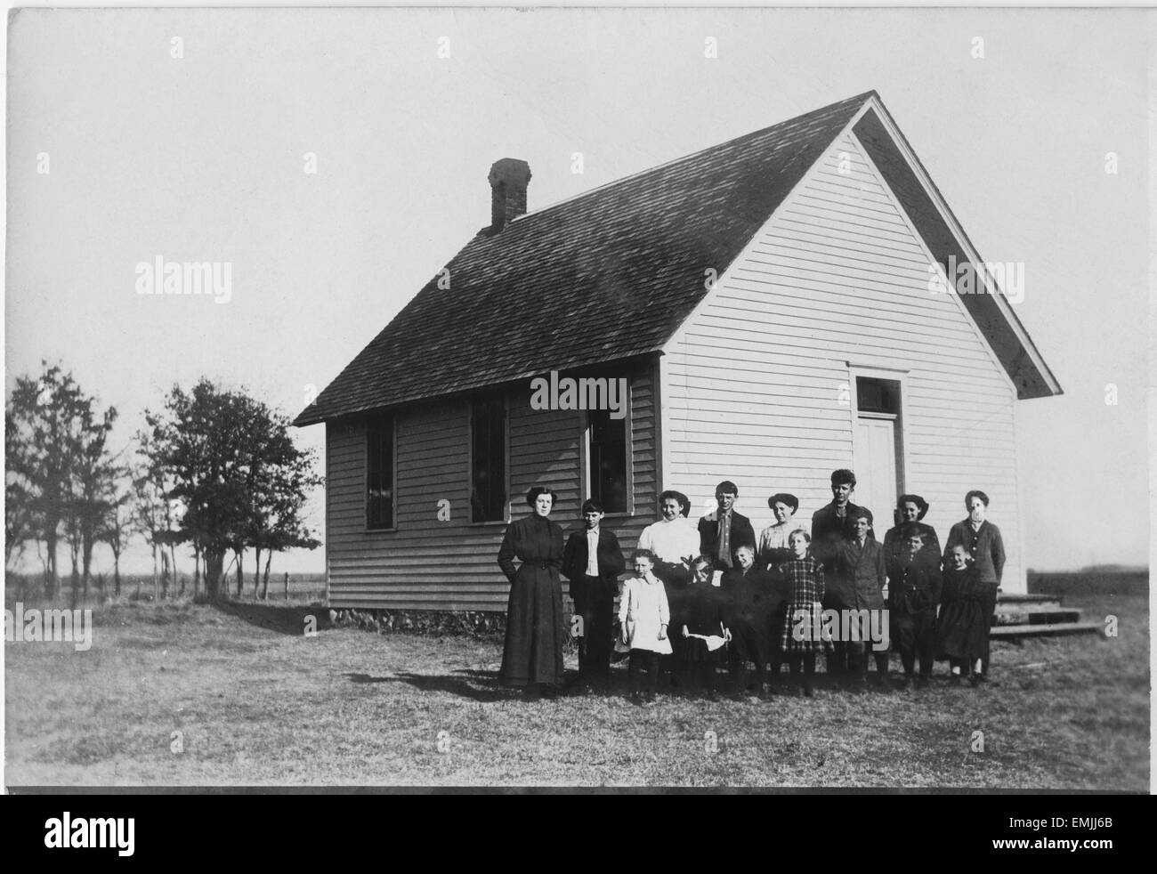 Teacher And Students In Front Of One Room School House