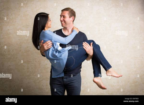 Man carrying woman in his arms Stock Photo - Alamy
