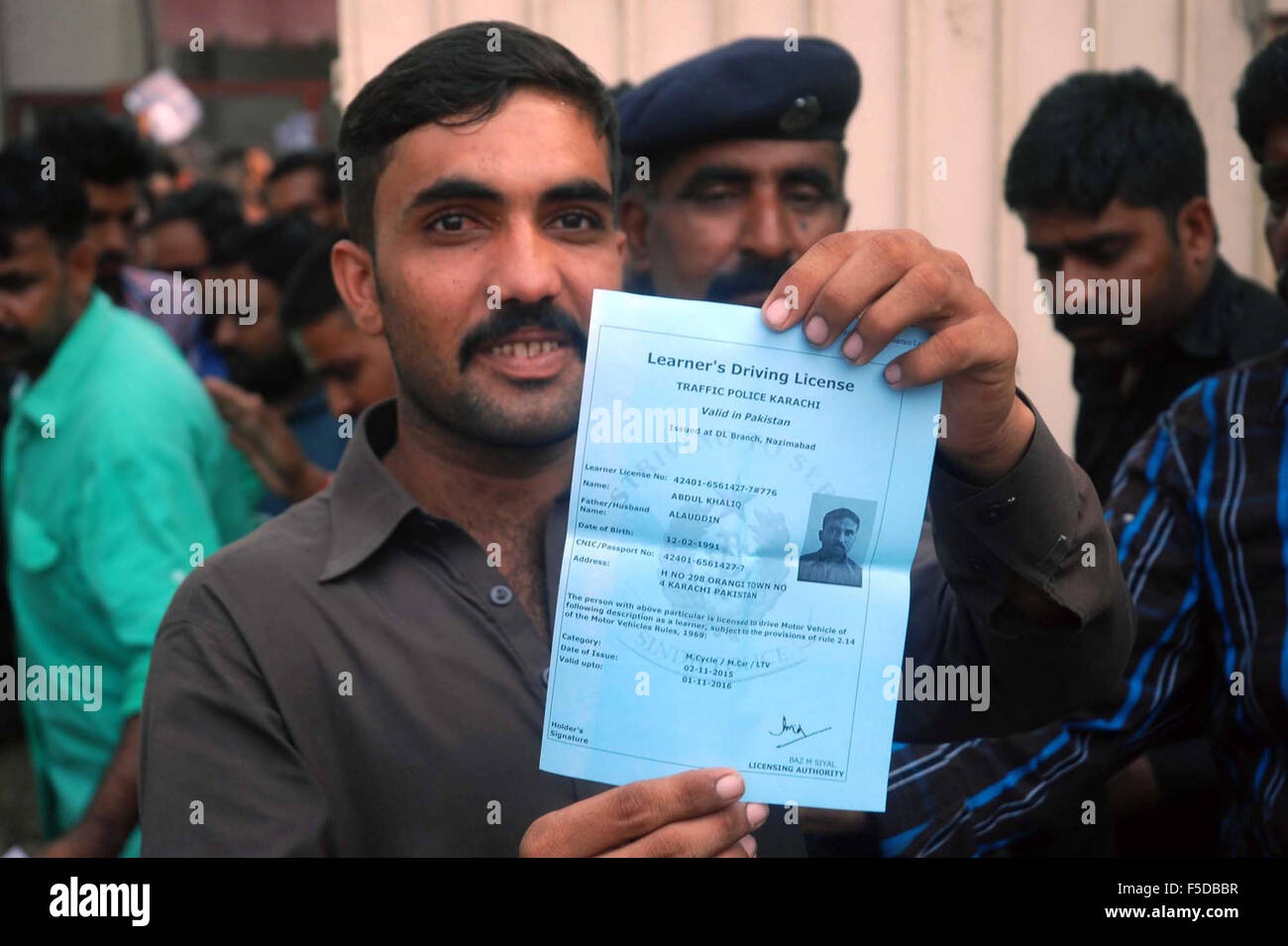 A Resident Of Karachi Showing His Learners Driving License Whereas The Large Numbers Of Residents Of Karachi Are Gathering At Traffic Police Office To Get