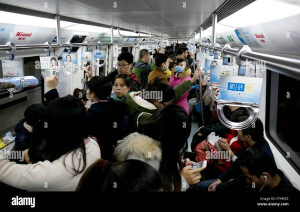 Subway riders in crowded subway car in Beijing, China ...