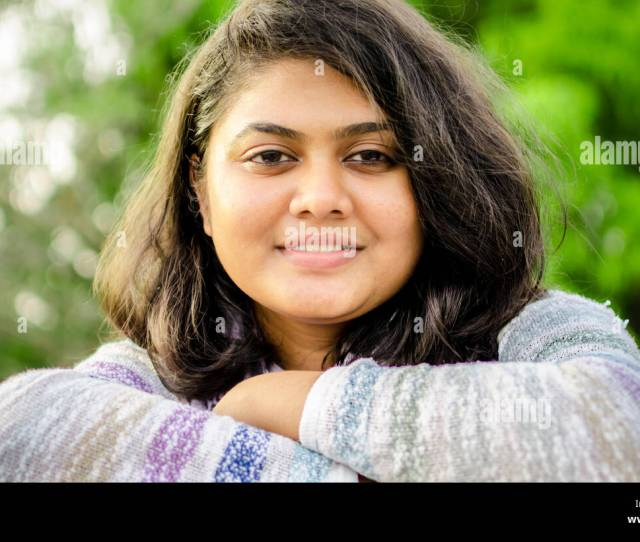 Close Up Portrait Of A Fair Chubby Indian Teenage Girl Folded Hands Looking At Camera