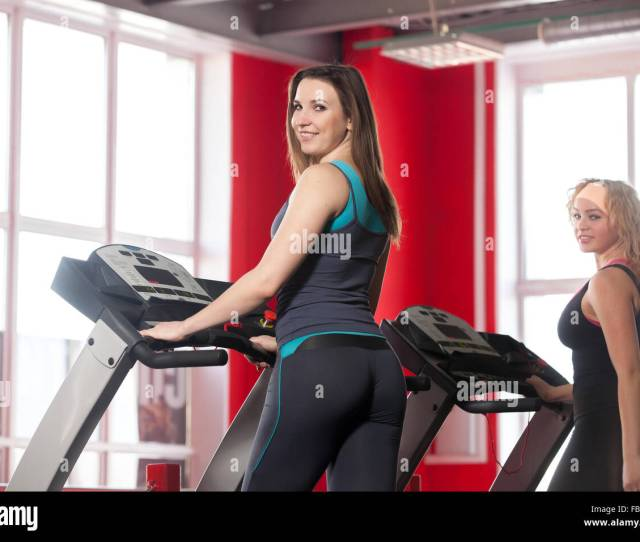 Two Sporty Girls In Sportswear Walking On Cardio Trainer Treadmill In Gym