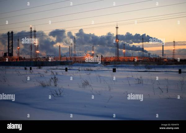 Refinery at sunset sky background. Frosty snowy winter ...