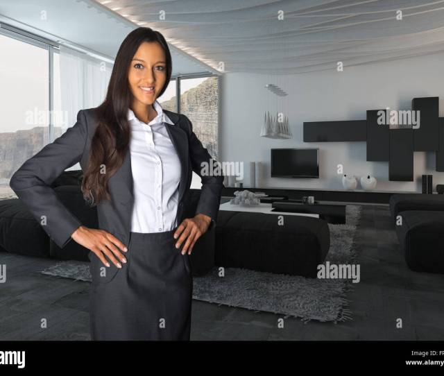 Close Up Young Female Agent Posing At Architectural Living Room While Looking At The Camera