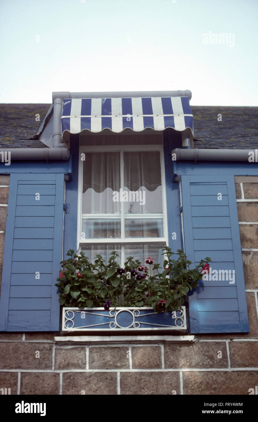 Exterior Of Small House With Striped Awning On Window With