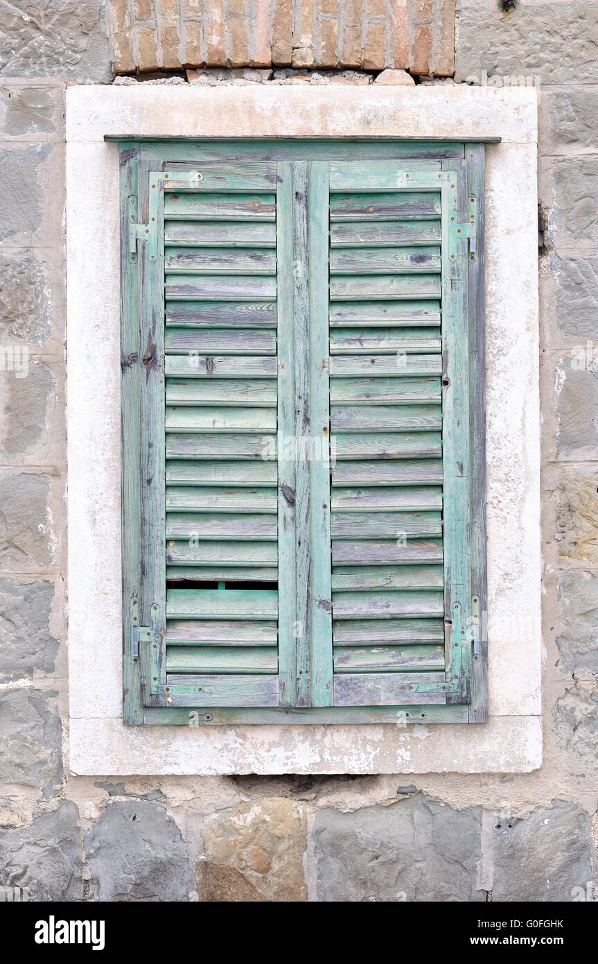 The Old Window With Blue Closed Shutters On An Old House