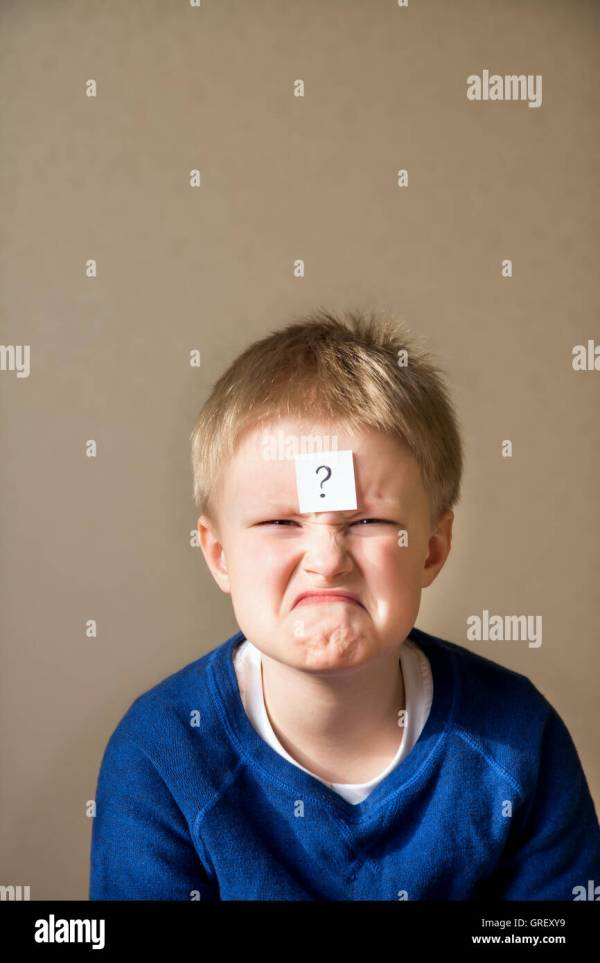 funny confused young boy with question mark on gray ...
