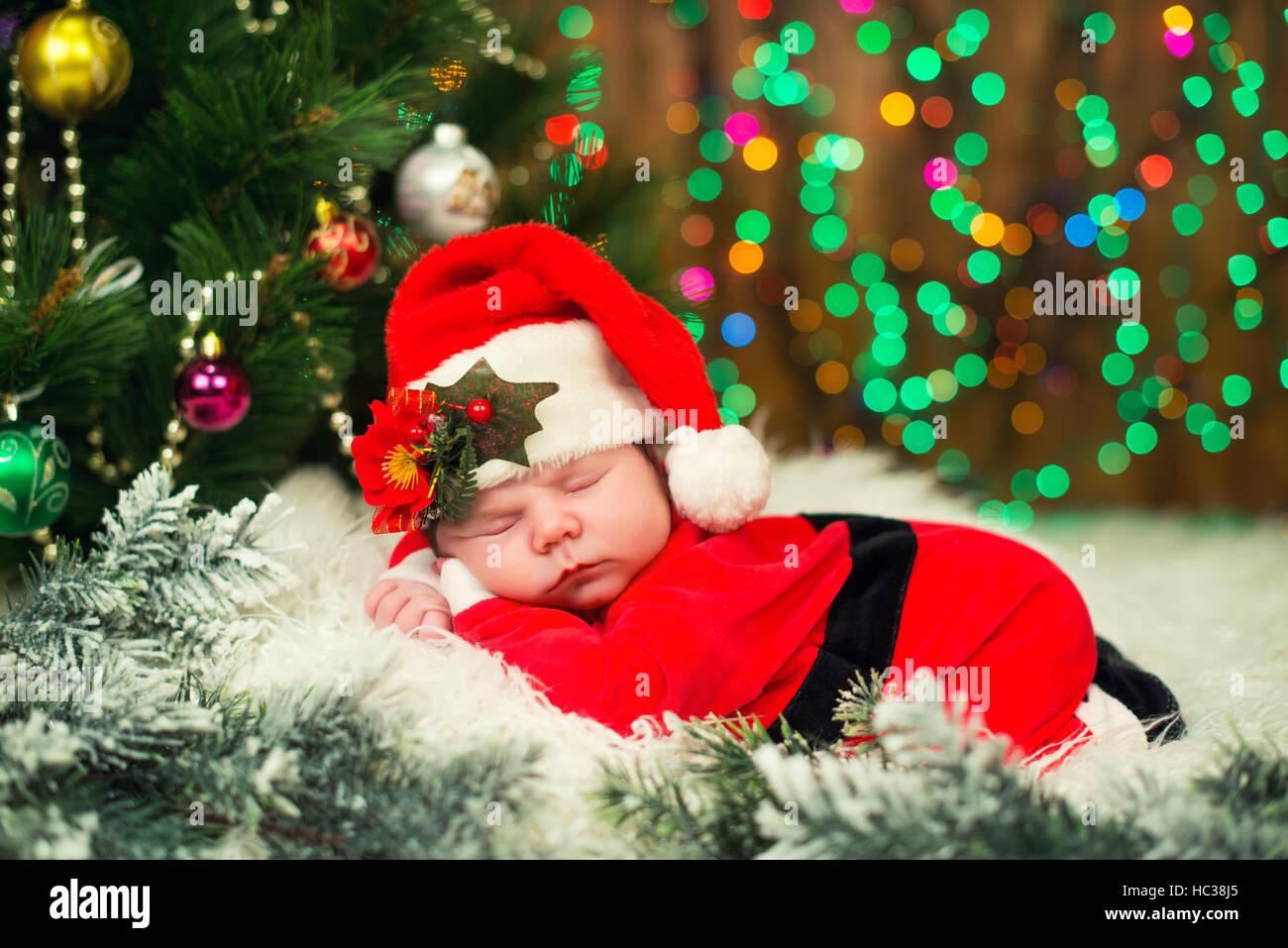 Portrait Of Newborn Baby In Santa Clothes Lying Under