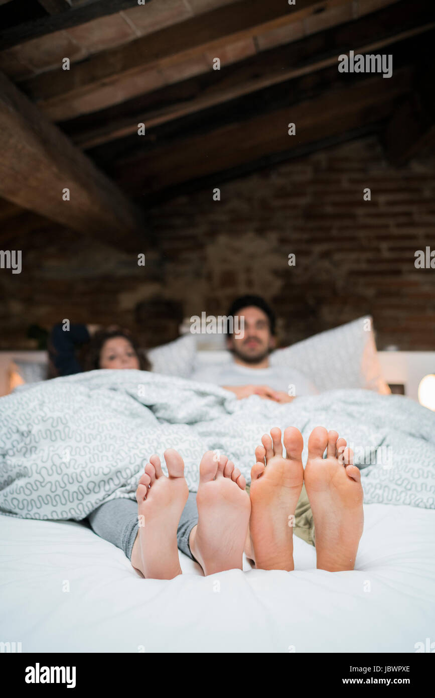 Bare Feet Soles Of Young Couple Lying In Bed Stock Photo