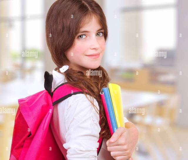 Side View Of Cute Teen Girl Standing In Classroom With Colorful Books In Hands And Bright Pink Backpack On Shoulders Preparing To Lesson Back To School