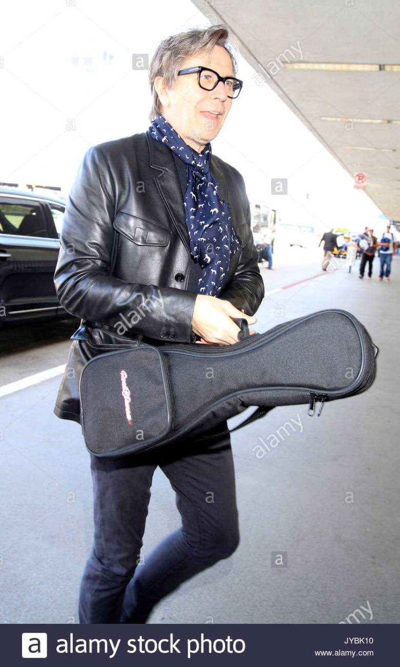 gary oldman. gary oldman carries a musical instrument in los angeles
