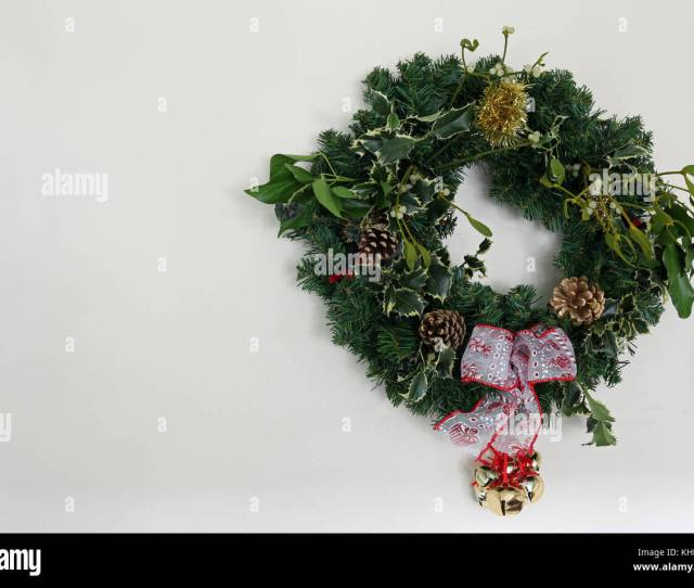 Home Made Christmas Wreath With Holly Mistletoe Pine Cones Ivy Tinsel Ribbon Artficial Conifer Twigs And Bells Against A Light Background With C