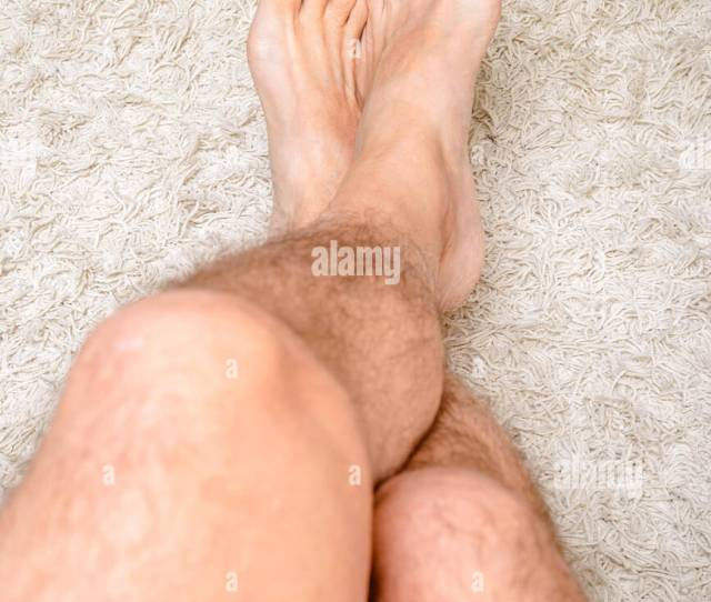 A Man Is Relaxing The Feet On A Warm Wool Carpet And Showing Hairy