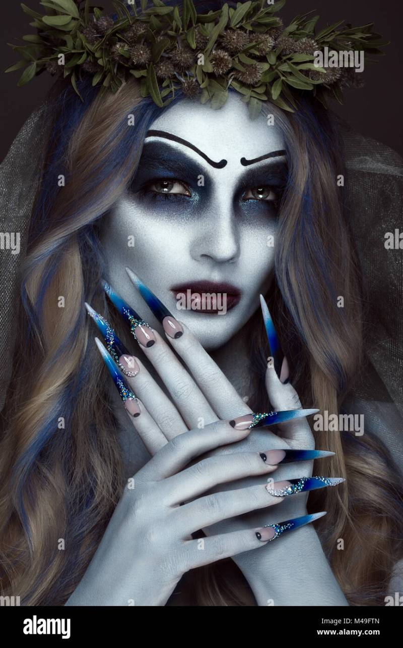 Portrait Of A Horrible Corpse Bride In Wreath With Flowers Halloween Makeup And Long Manicure Design Nails