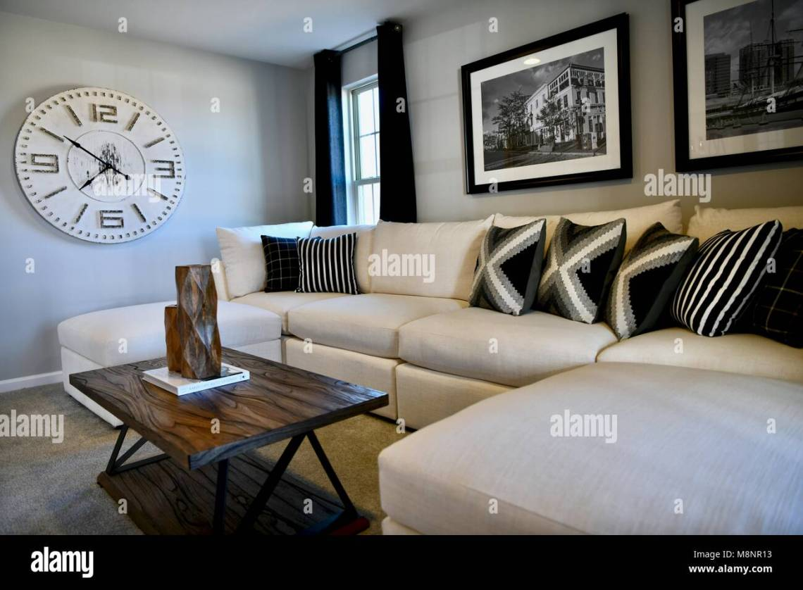 Living Room With White Sectional And Modern Decor On The Walls Stock Photo Alamy