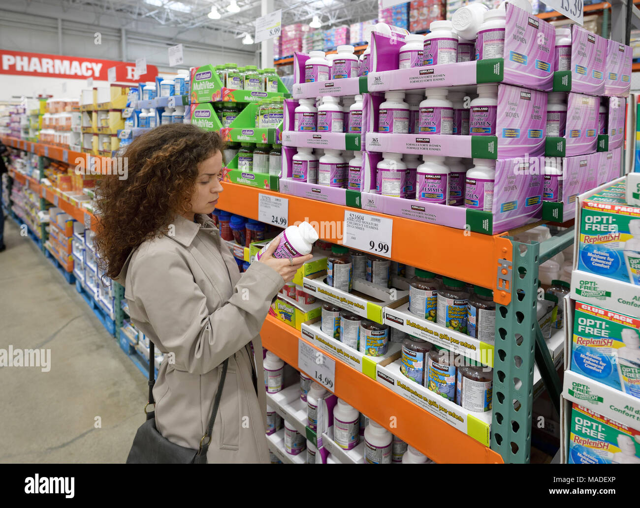 Woman reading indredients of Kirkland Women formula ... on Kirkland Costco Pharmacy id=38407