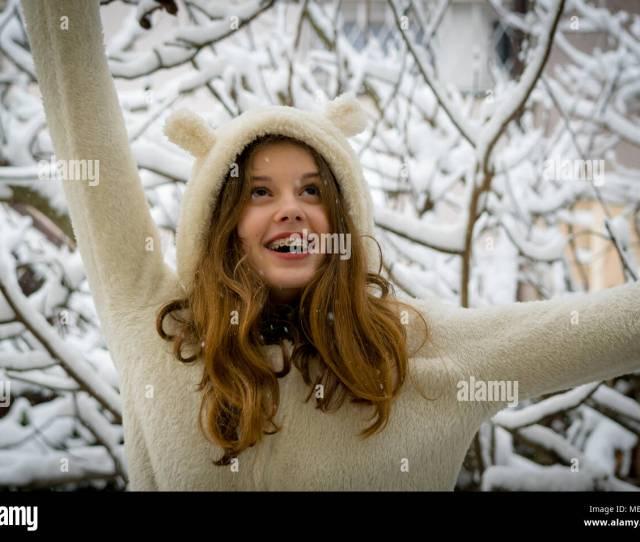 Portrait Of Cute Happy Teenage Girl In Snow Winter Theme Closeup Beautiful Teen Girl Long Hair White Coat Smiling In Snow