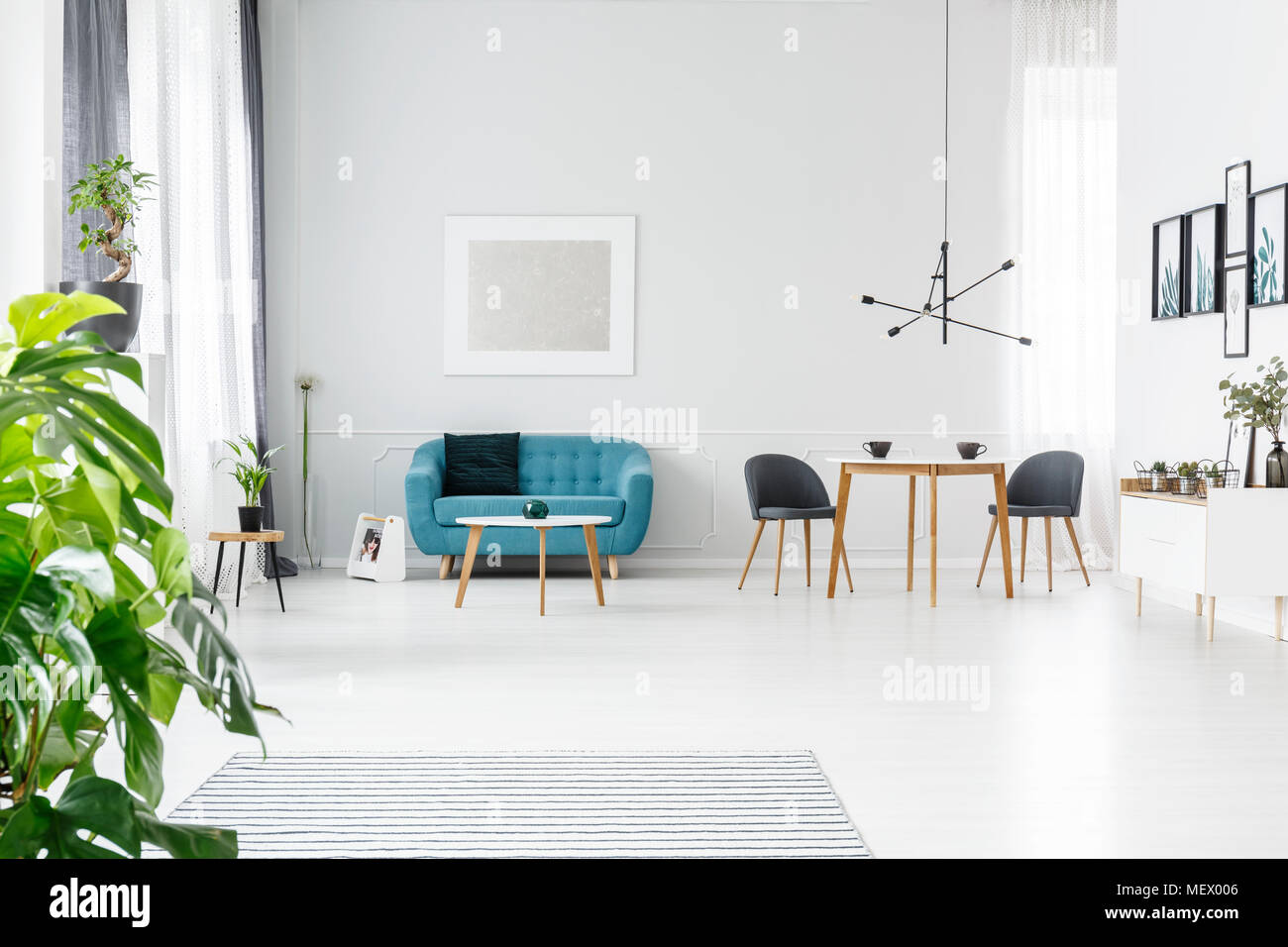 https www alamy com bright spacious and elegant flat for sale with posters coffee cups on wooden table and turquoise couch image181279622 html