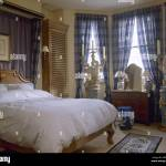 Blue Bedroom With Double Bed And Fabric Canopy Behind Wooden Headboard Window With Check Curtains Stock Photo Alamy