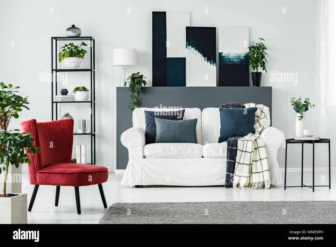 Red Armchair White Comfy Sofa With Blue Pillows And Plants In An Elegant Living Room Interior Stock Photo Alamy
