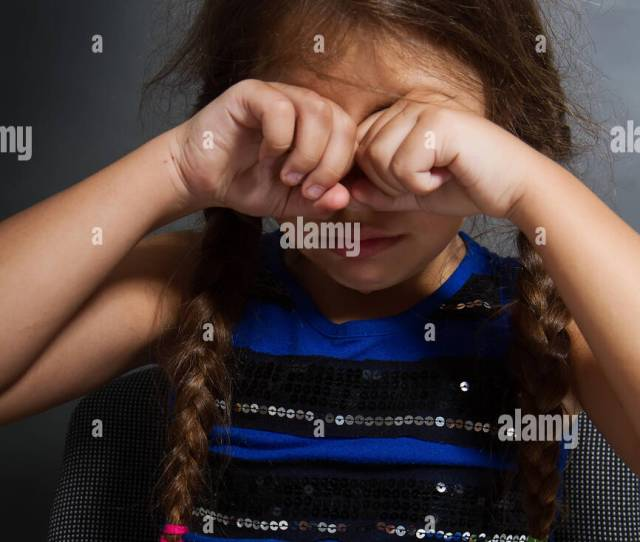 A Little Girl With Two Pigtails Sits And Weeps Bitterly On A Grubby Gray Background