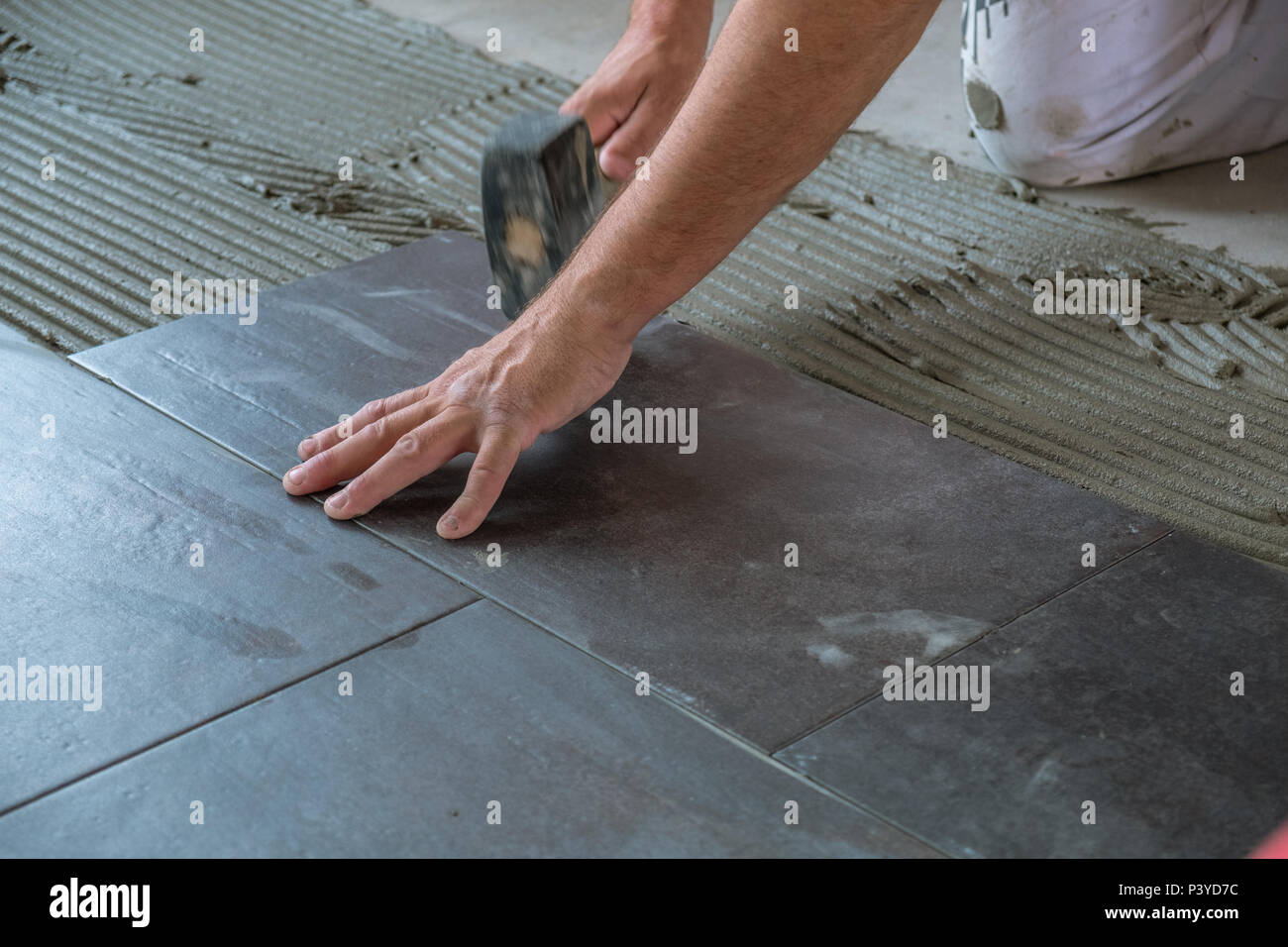 https www alamy com worker placing ceramic floor tiles on adhesive surface leveling with rubber hammer image208971488 html