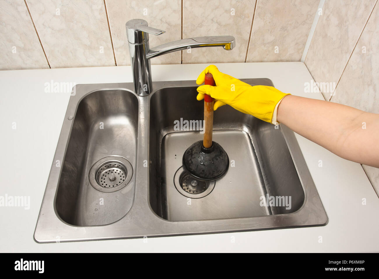 https www alamy com hand using a plunger to cleaning a clogged kitchen sink image210799030 html