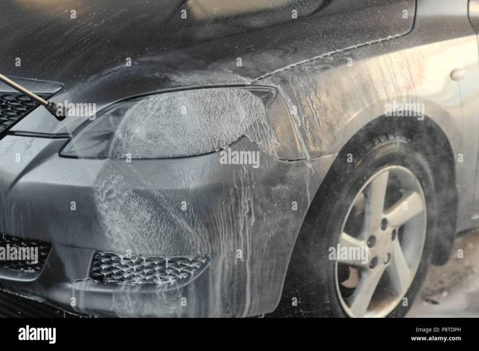 cleaning the car, car care concept - car washing under high pressure