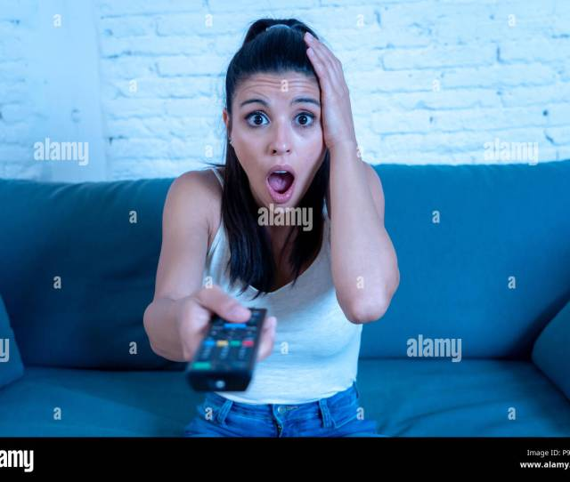 Young Beautiful Latin Woman Sitting At Home Sofa Couch In Living Room Watching Television Scary Horror Movie Or Horrible News Scared And Excited Cover