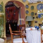 Collection Of Blue White Plates On Walls Of Yellow Conservatory Dining Room With Arched Doorway Stock Photo Alamy
