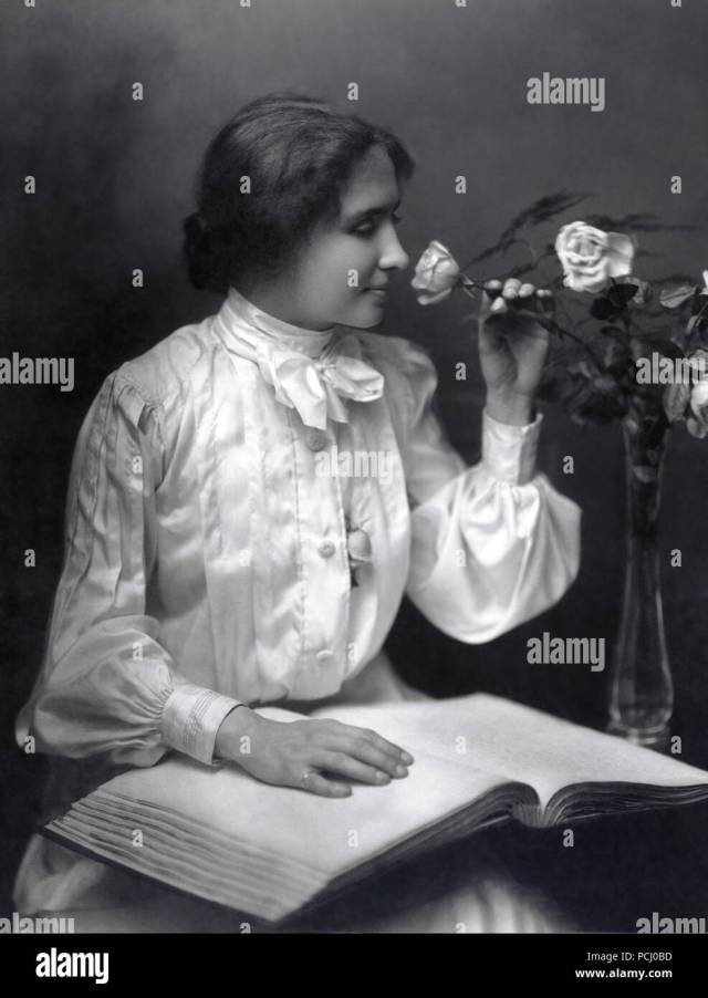 Helen Keller, seated seated with hand on braille book in her lap