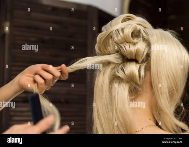 hairdresser does hairstyle for luxurious blond woman