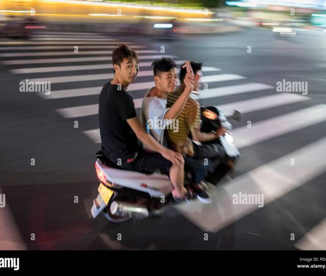 Three Teen Boys Wave While Pass By On Motor Scooter Speed Through City Center On Hot Summer Night Libo Guizhou Province China