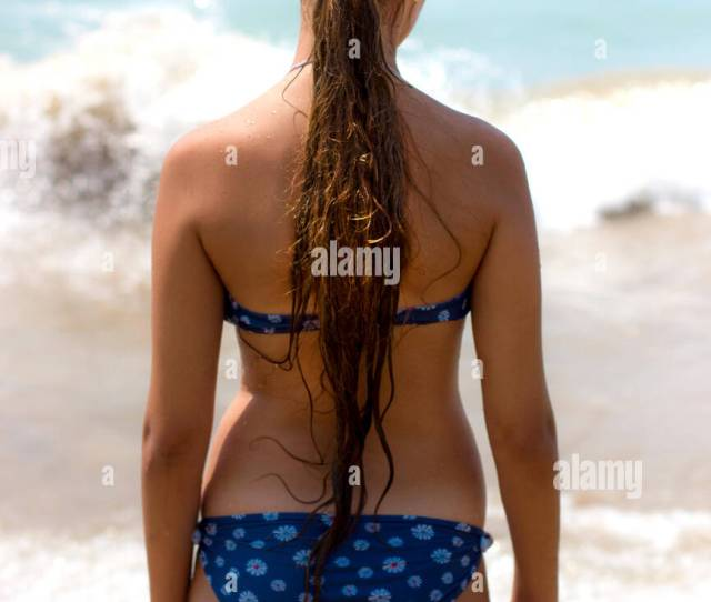 Slim Tanned Girl With Long Hair Goes To The Sea Along The Sandy Beach
