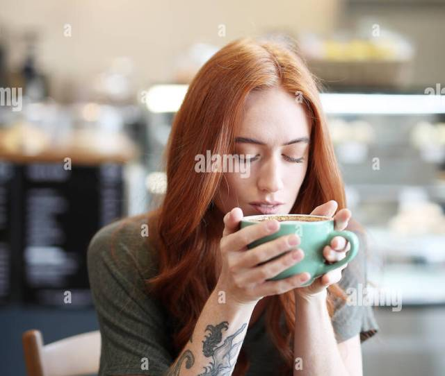 Redhead Single Female Sits In A City Cafe Holding A Hot Beverage In A Cup