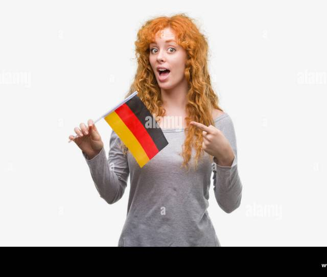 Young Redhead Woman Holding Flag Of Germany Very Happy Pointing With Hand And Finger Stock
