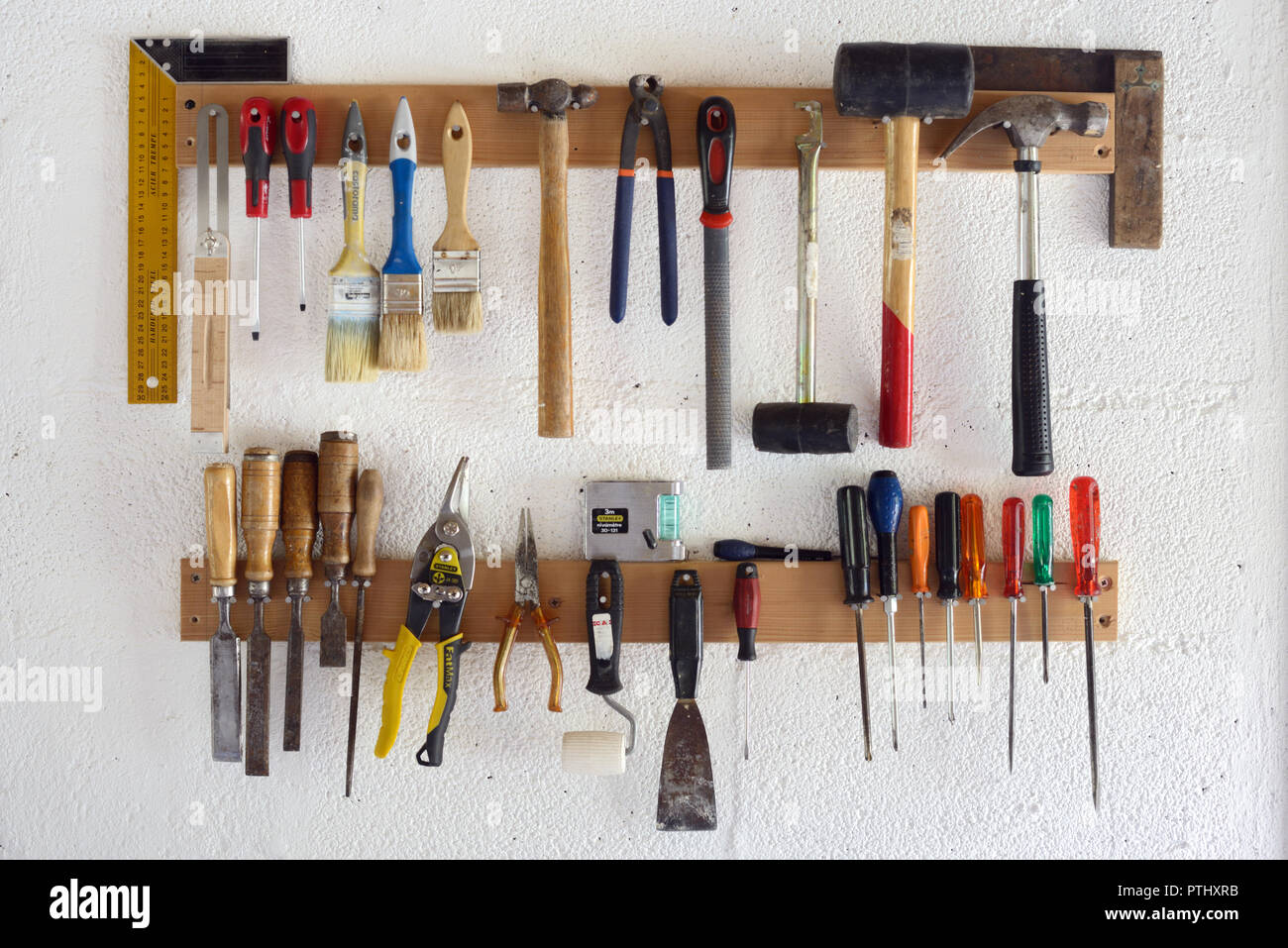 https www alamy com woodworking tools hand tools including screw drivers paint brushes and hammers hanging in workshop or garage wall mounted tool rack image221670383 html