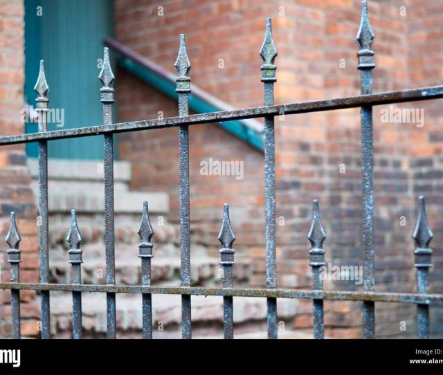 Antique Wrought Iron Fence With Selective Focus Brick Wall With Doorway And Staircase In The Background