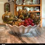 Bowl Of Artichokes And Grapes On Granite Countertop In Country Kitchen With Large Open Hutch In Background With White Dishes Stock Photo Alamy
