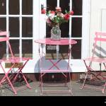 Outside Table And Chairs With A Vase Of Flowers For