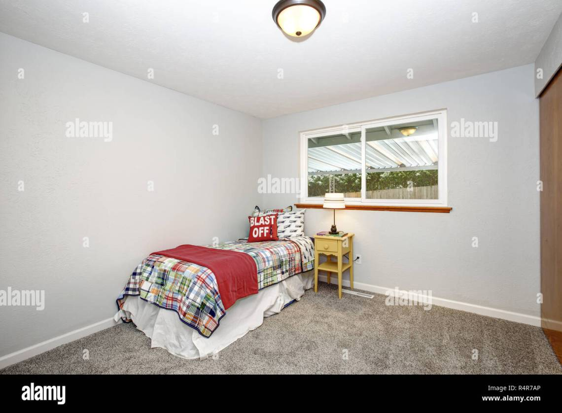 Kids Minimal Bedroom With Colorful Bedding Grey Walls And Wall To Wall Carpet Stock Photo Alamy