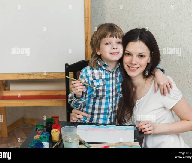 Young Beautiful Mother With Boys Son Paint Colors At Home Mom Teaches Son To Paint Colors