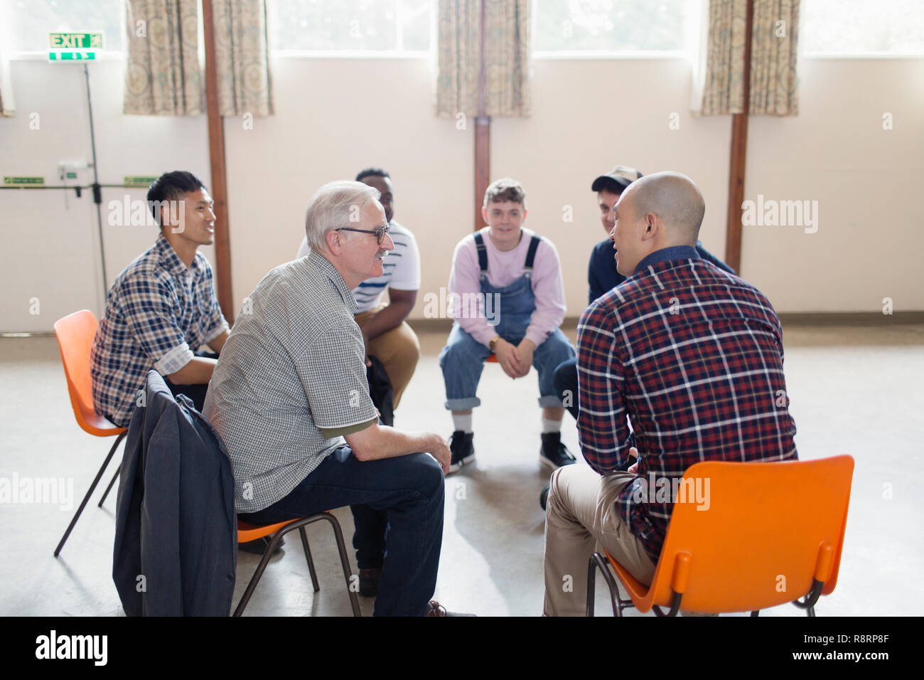Men Talking In Group Therapy Circle Stock Photo