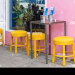Four Bright Yellow Stools Against A Pink Background Curacao Stock Photo Alamy