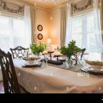 Set Antique Wooden Dining Table With 1850s Dishes And Hand Sculptured Sitting Chairs In Dining Room