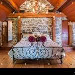 King Size Bed With Antique Wrought Iron Headboard And Footboard In Master Bedroom With Wide Pinewood