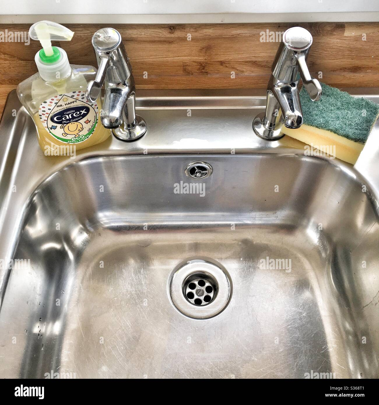 https www alamy com a photograph of a spotlessly clean stainless steel sink and taps with a bottle of carex hand soap and a sponge cleaning clean home ocd washing hands concept image311769249 html
