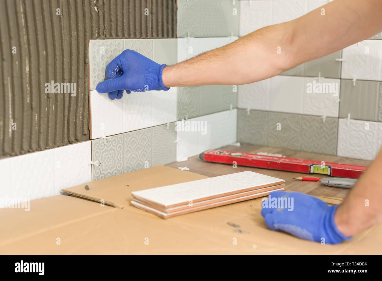 https www alamy com closeup of tiler hand laying ceramic tile on wall in kitchen renovation repair construction image242887447 html