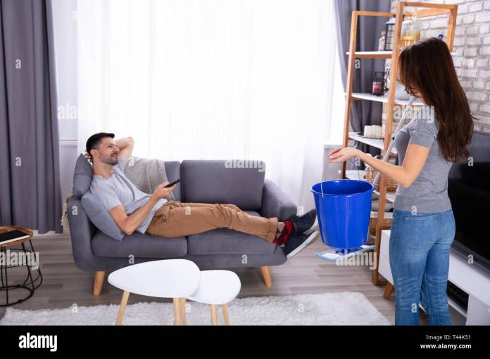 Woman's Hand Holding Bucket And Mop Standing In Front Of Lazy Man ...