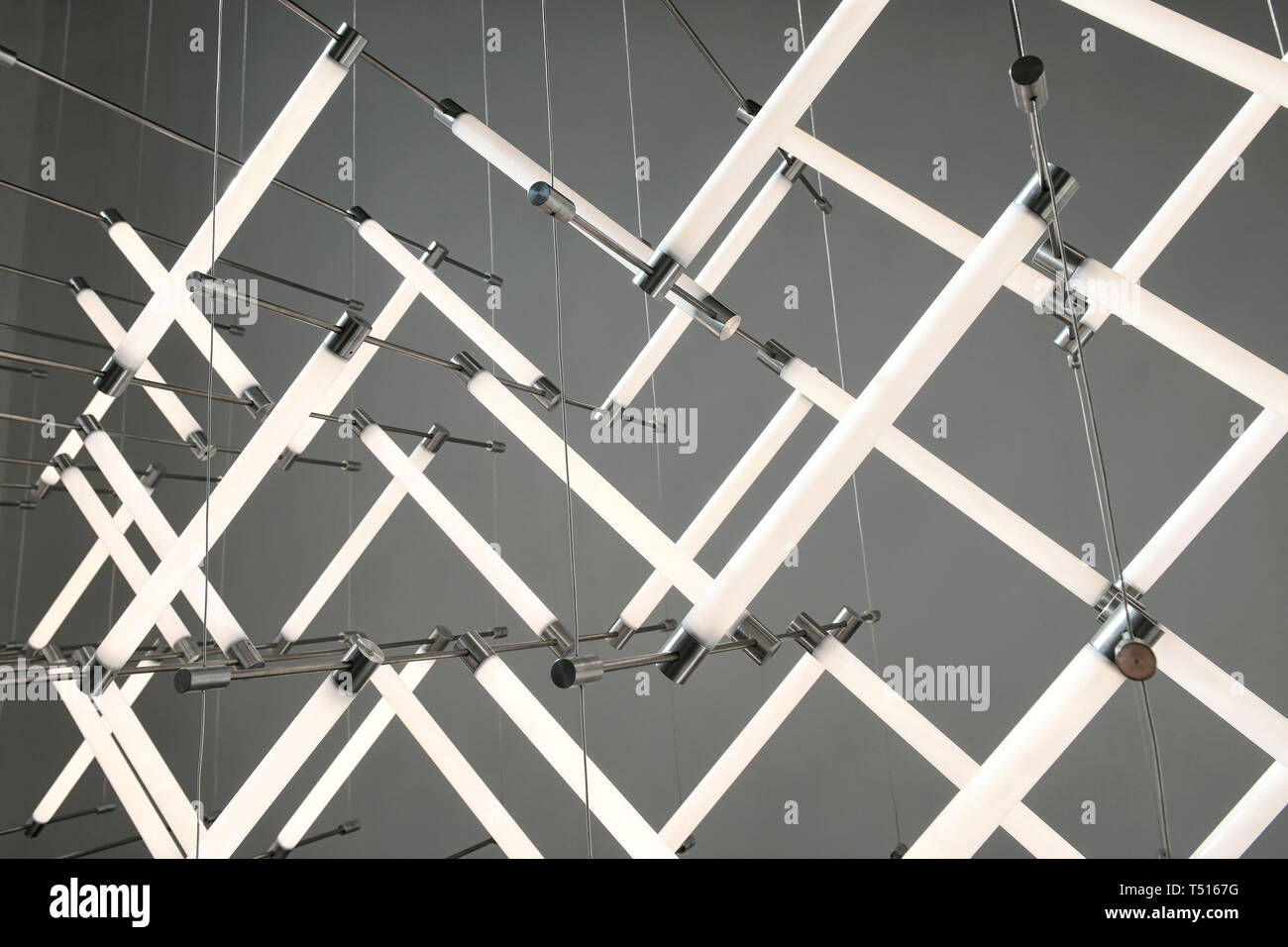 https www alamy com close up on modern neon lighting design with white stick lamps hanging on thin metal threads viewed in close up against grey wall image244045300 html